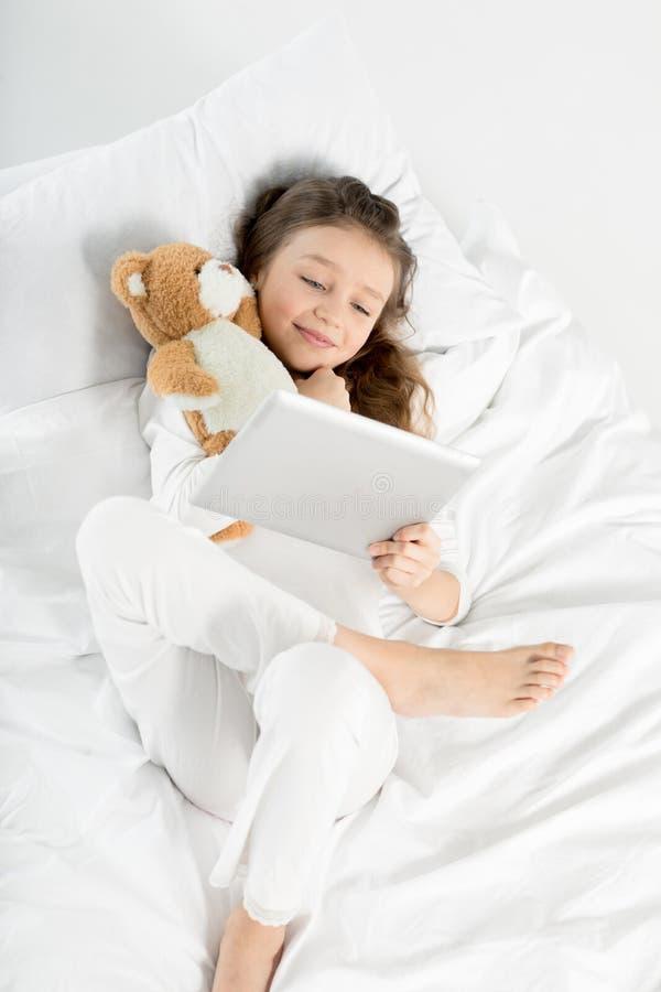 Menina nos pijamas usando a tabuleta digital ao encontrar-se na cama fotografia de stock