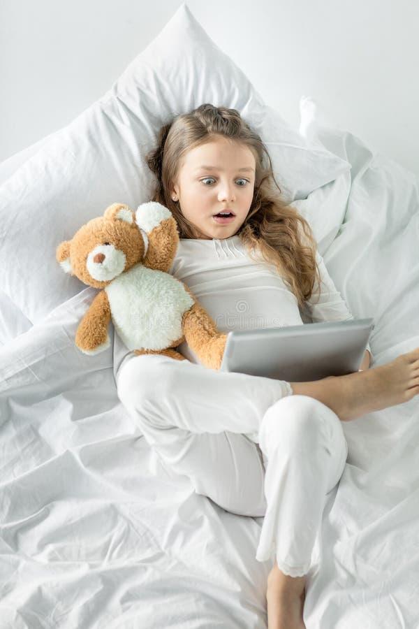Menina nos pijamas usando a tabuleta digital ao encontrar-se na cama foto de stock royalty free