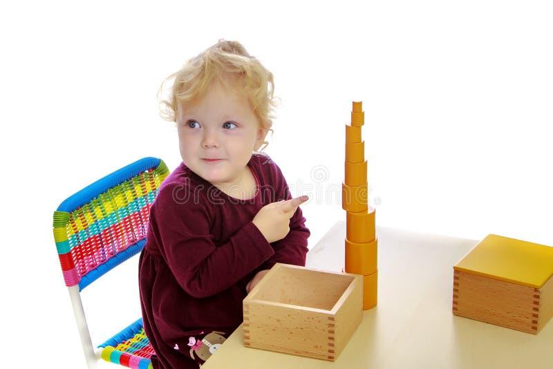 A menina nos trabalhos da tabela com o material de Montessori fotos de stock royalty free