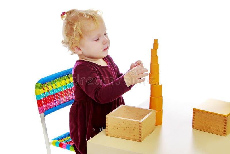 A menina nos trabalhos da tabela com o material de Montessori foto de stock