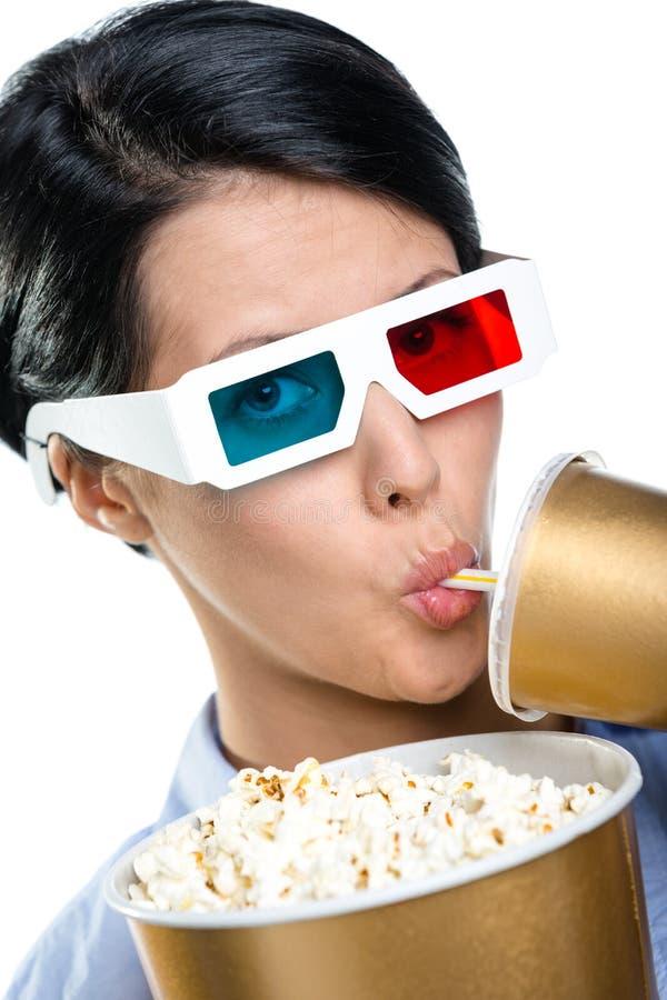 Menina nos vidros 3D com bebida e bacia de pipoca fotografia de stock royalty free
