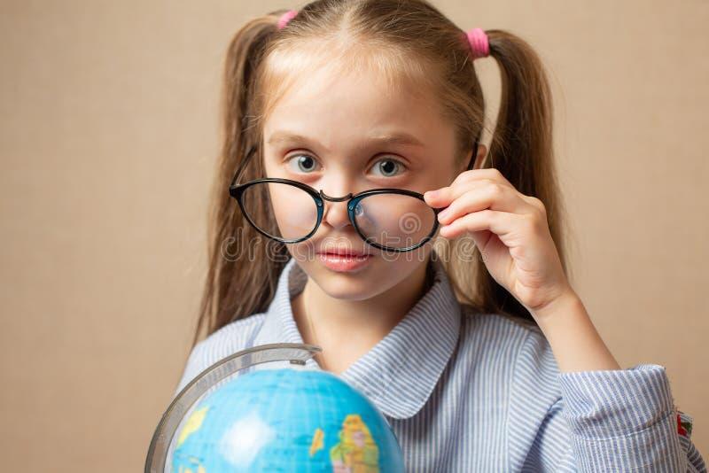 Menina nos vidros que guardam o globo foto de stock royalty free