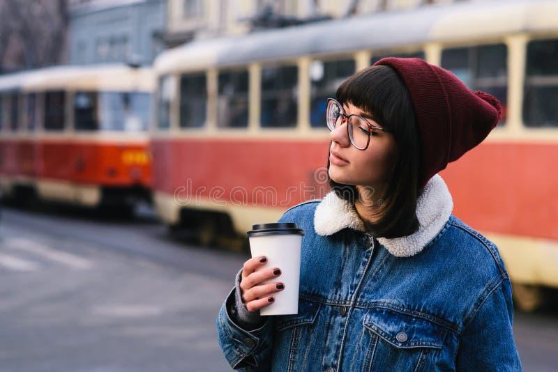 A menina nova à moda do moderno anda na cidade e no café bebendo no fundo do bonde fotografia de stock