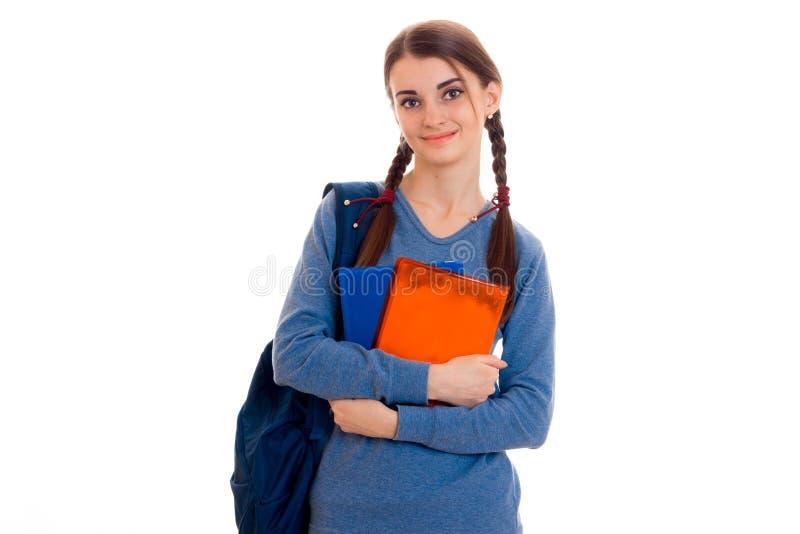 Menina nova alegre do estudante com a trouxa e os livros que olham a câmera e sorriso isolado no fundo branco foto de stock royalty free