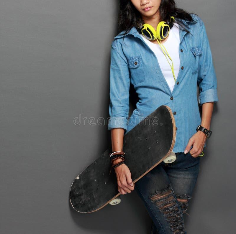 Menina nova asiática do skater que guarda um skate fotos de stock