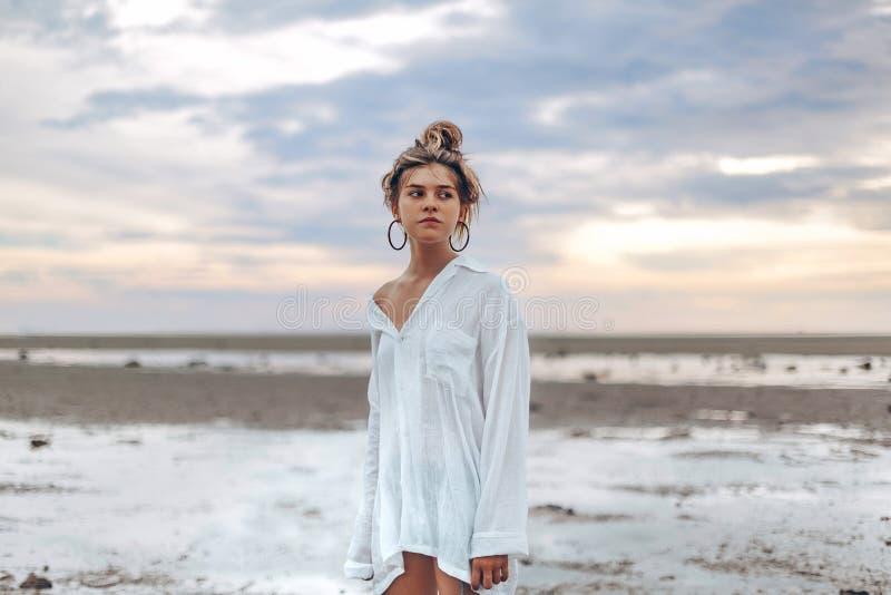 Menina nova bonita do estilo do boho na praia no por do sol na novo imagem de stock