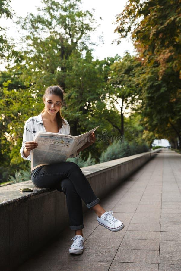 Menina nova bonita do estudante que senta-se fora fotos de stock royalty free