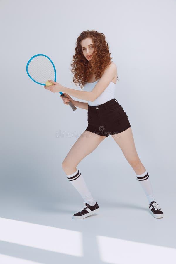 Menina nova bonita do moderno que joga o tênis com raquete e bola imagens de stock