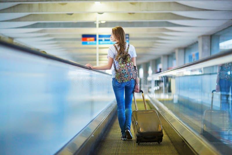 A menina nova bonita do turista com trouxa e continua a bagagem no aeroporto internacional fotografia de stock royalty free