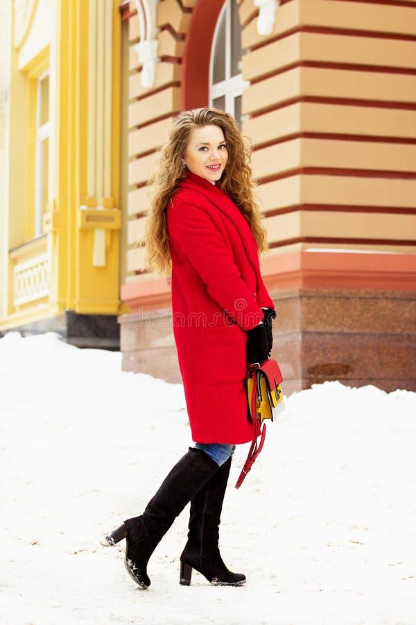 Menina nova, bonita e à moda do cabelo louro no revestimento vermelho e com bolsa que anda através das ruas da cidade A forma das foto de stock