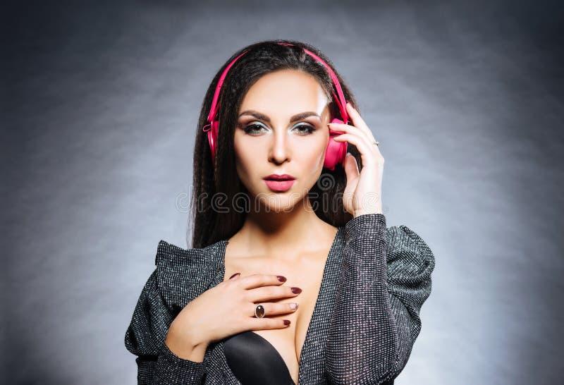 Menina nova, bonita e 'sexy' do DJ que escuta a música no fones de ouvido imagem de stock