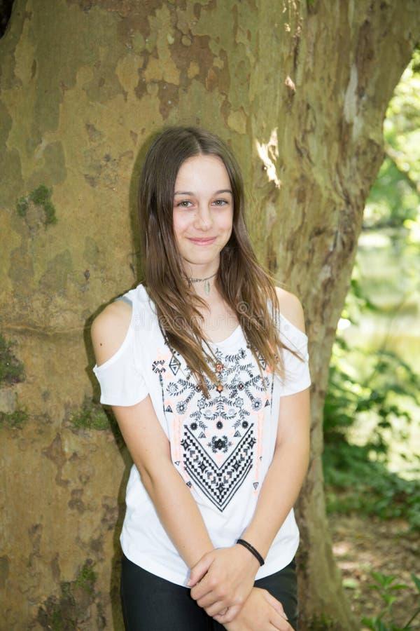 Menina nova bonito do adolescente contra a árvore no verão imagem de stock