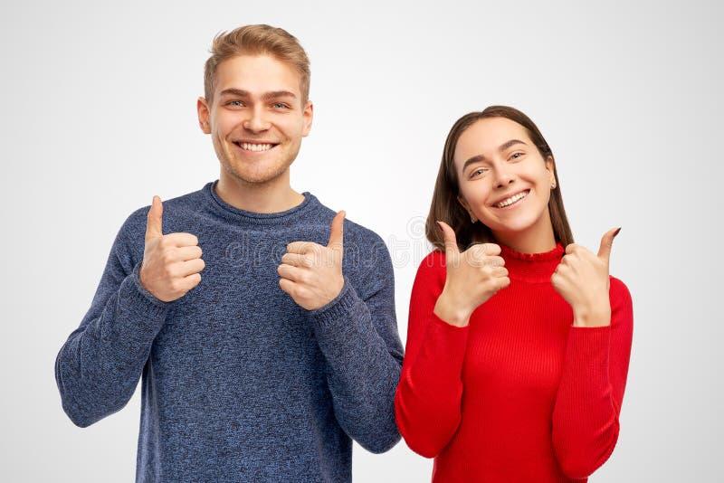 Menina nova bonito e homem dos pares que têm o divertimento que sorri e que mostra os polegares acima do sinal Sinal do divertime imagens de stock royalty free
