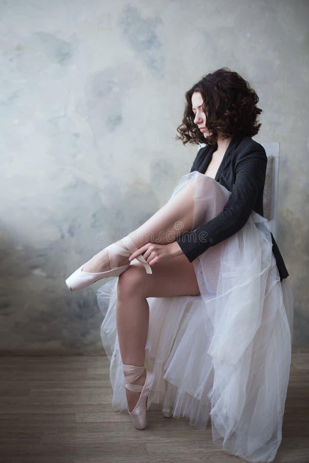 Menina nova da bailarina ou do dançarino que põe sobre suas sapatas de bailado fotos de stock