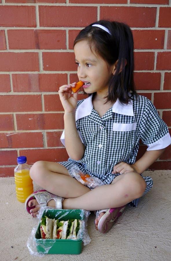 Menina nova da escola que come seu almoço. fotografia de stock royalty free