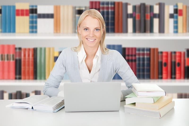 Menina nova da estudante universitário em uma biblioteca fotografia de stock