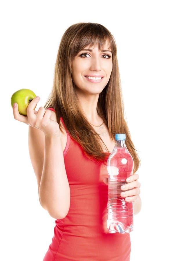 Menina nova da felicidade com garrafa da água e de uma maçã fotos de stock royalty free