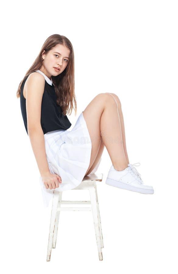 Menina nova da forma na saia branca que senta-se na cadeira isolada imagem de stock