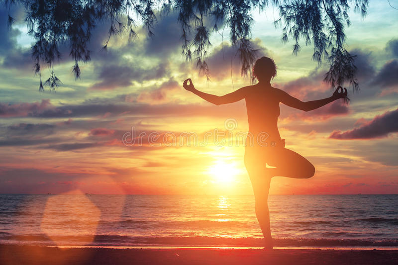 Menina nova da ioga que pratica na praia do oceano em por do sol bonito surpreendente nave fotografia de stock