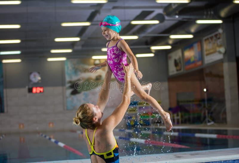 Menina nova da mãe e do pré-escolar que tem o divertimento no po nadador interno foto de stock royalty free