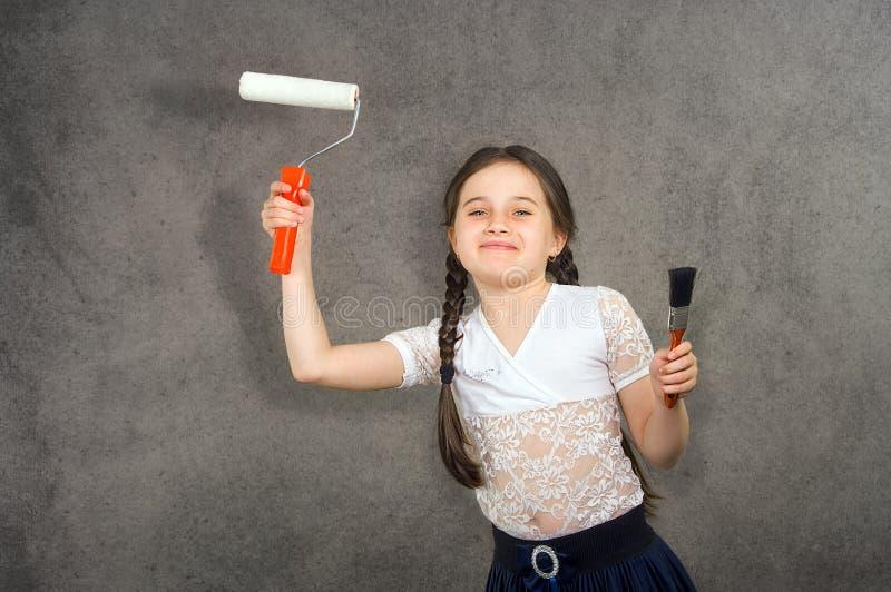 A menina nova de sorriso alegre a criança tira nas cores da parede do fundo a fatura de reparos criativos fotografia de stock