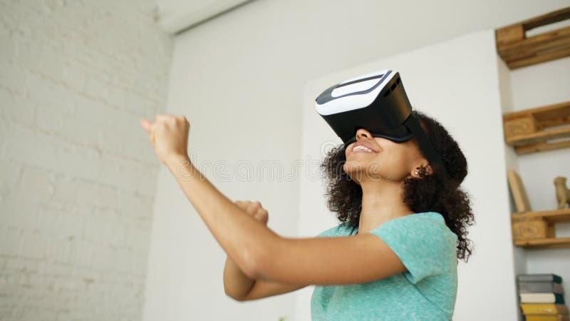 Menina nova de sorriso feliz da raça misturada que obtém a experiência usando vidros dos auriculares de VR da realidade virtual e imagens de stock
