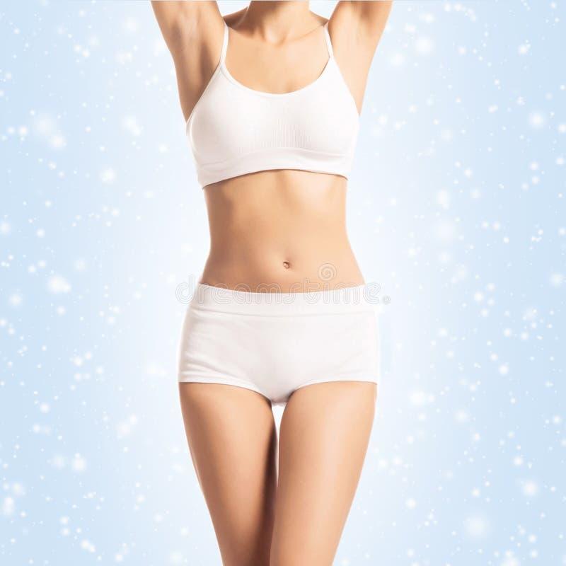 Menina nova, desportiva, apta e saudável sobre o fundo do inverno Corpo fêmea desportivo no roupa interior branco do emagreciment imagem de stock royalty free