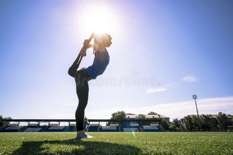 Menina nova, desportiva aquecer-se antes de uma sessão de formação no estádio No sportswear foto de stock