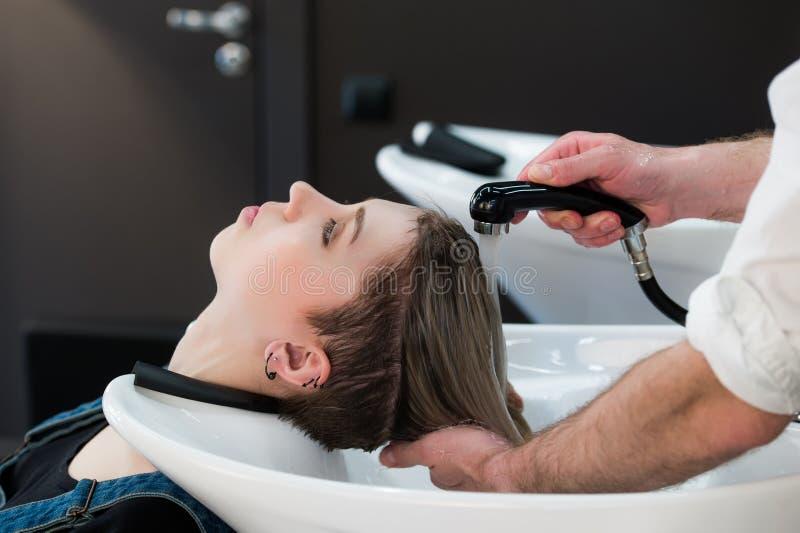 Menina nova do adolescente no cabelo de lavagem do salão de beleza do cabeleireiro pelas mãos do cabeleireiro masculino imagens de stock royalty free