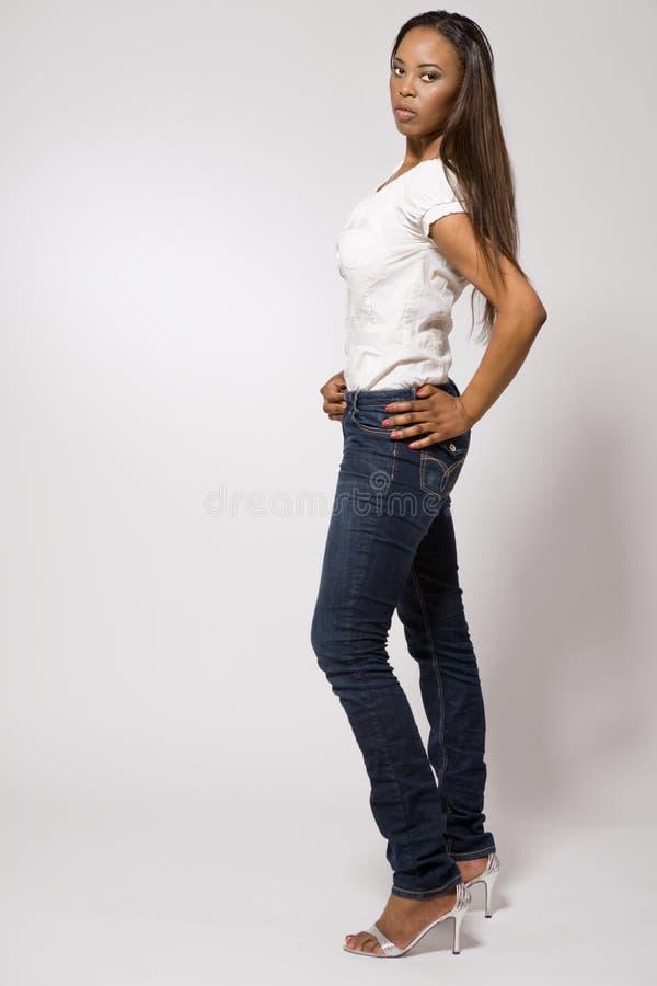 Menina nova do african-american na calças de ganga. imagens de stock