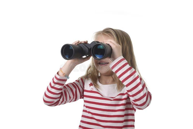 Menina nova do cabelo louro que olha guardando os binóculos que olham com da observação e da observação curiosa fotos de stock royalty free