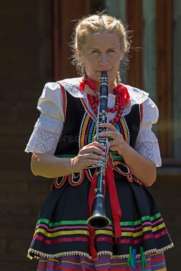 Menina nova do cantor no clarinete do Polônia no traje tradicional imagem de stock