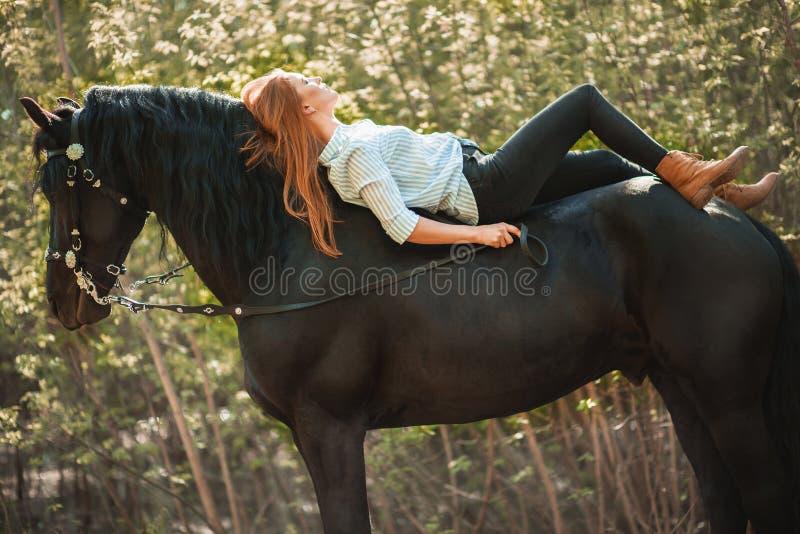 Menina nova do cavaleiro com o cabelo longo que encontra-se no pescoço do cavalo imagens de stock royalty free