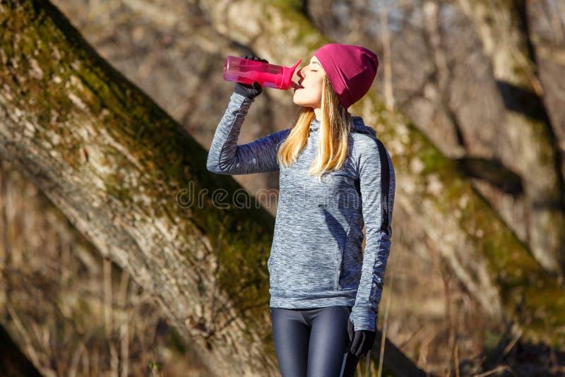 Menina nova do corredor com a garrafa da água no parque imagens de stock royalty free