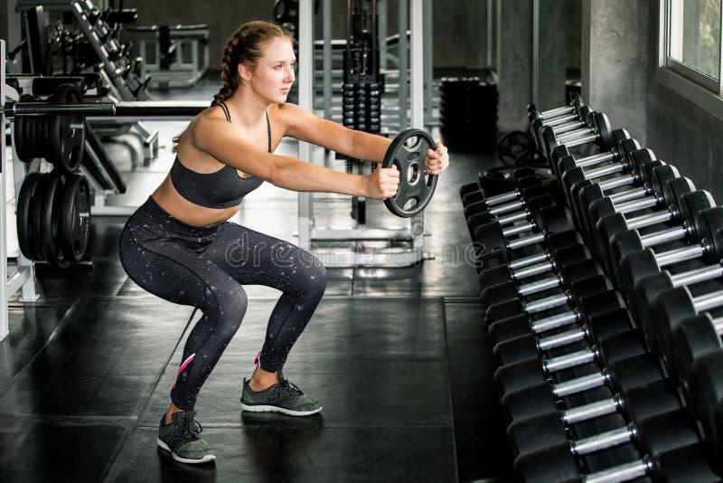 menina nova do esporte da aptidão que faz a ocupa do exercício com a placa do barbell do peso no gym a mulher no exercício do spo foto de stock