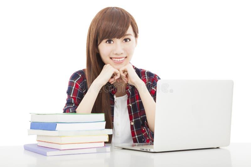 Menina nova do estudante com o livro e o portátil isolados no branco foto de stock