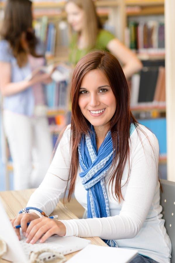 Menina nova do estudante no portátil de dactilografia da biblioteca imagem de stock
