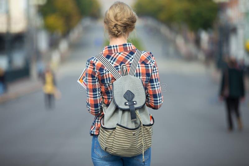 Menina nova do estudante que anda abaixo da rua com uma trouxa fotos de stock