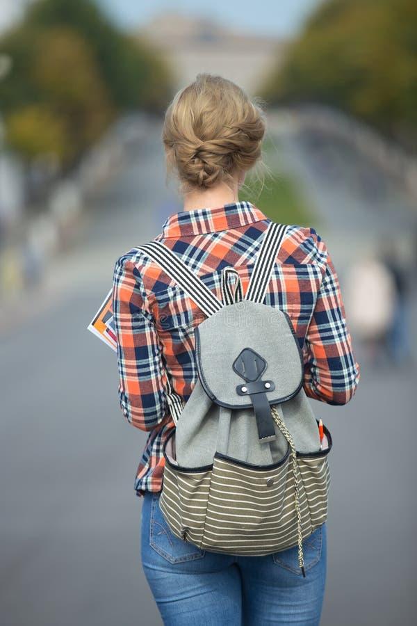 Menina nova do estudante que anda abaixo da rua com uma trouxa foto de stock