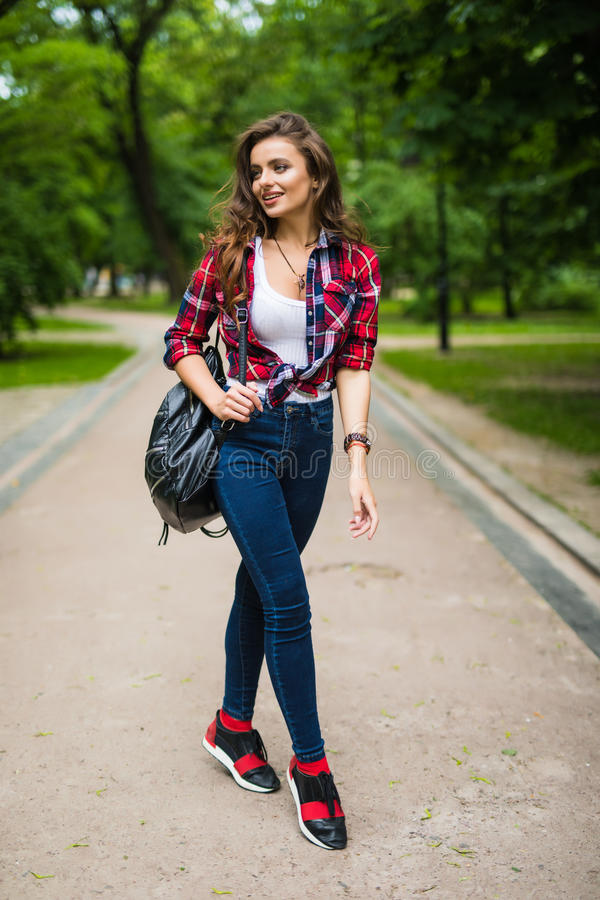 Menina nova do estudante que anda abaixo da rua com uma trouxa no parque foto de stock royalty free