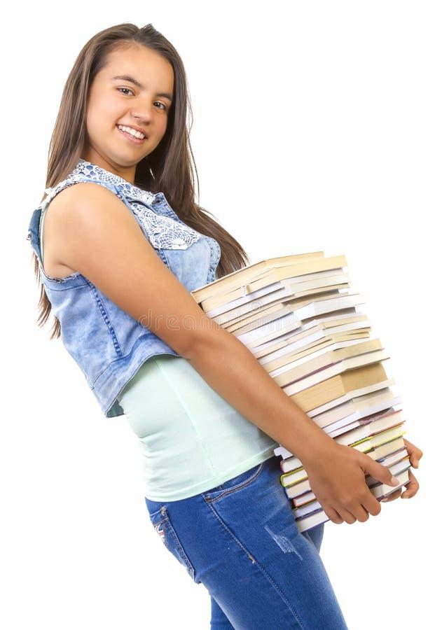 Menina nova do estudante que guarda uma pilha de livros imagens de stock