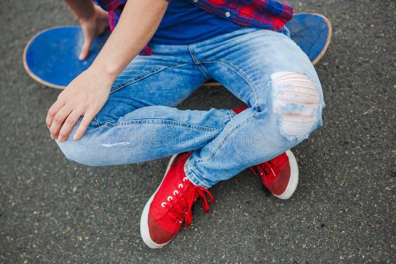 Menina nova do moderno com placa de patinagem na estrada imagem de stock royalty free