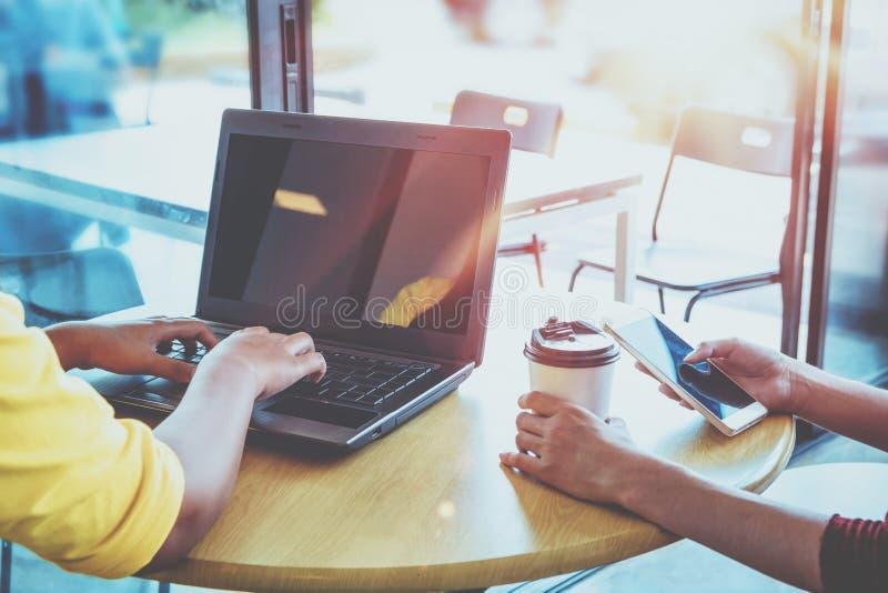 A menina nova do moderno dois entrega usando-se em seus portátil e telefone esperto que sentam-se na tabela de madeira em uma caf fotos de stock