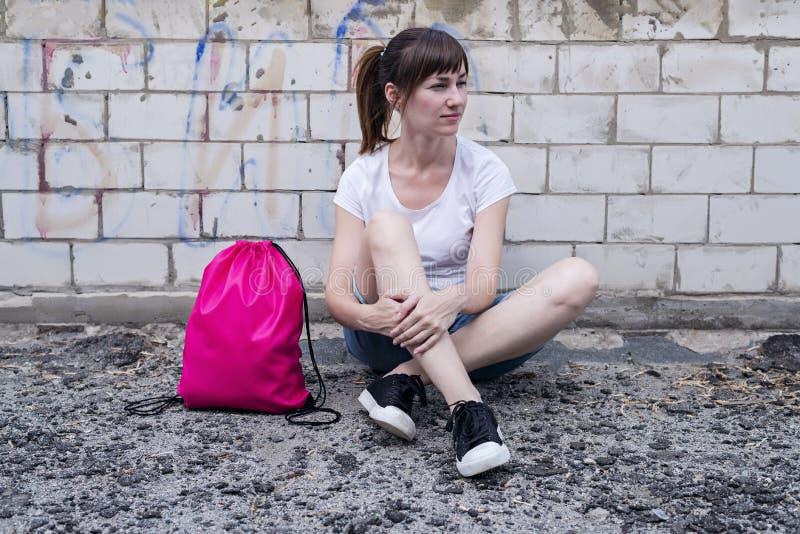 A menina nova do moderno está sentando-se na parede de tijolo com trouxa do cordão imagem de stock