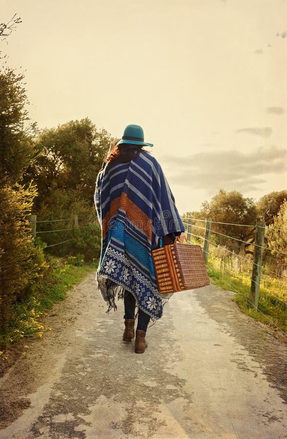 Menina nova do moderno no poncho com mala de viagem do vintage fotografia de stock royalty free