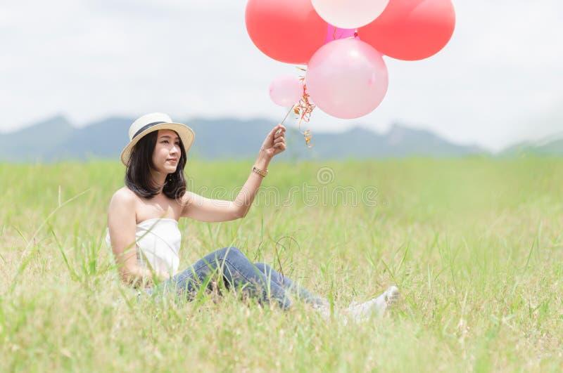 A menina nova do moderno que guarda o balão senta-se na grama, imagem de stock