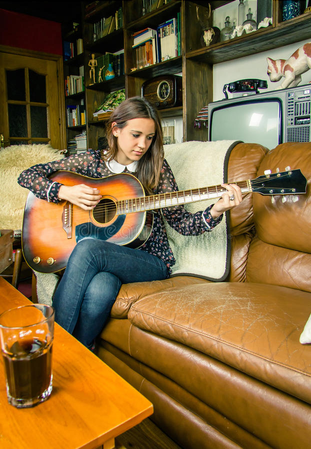 Menina nova do moderno que joga a guitarra acústica em casa fotos de stock royalty free