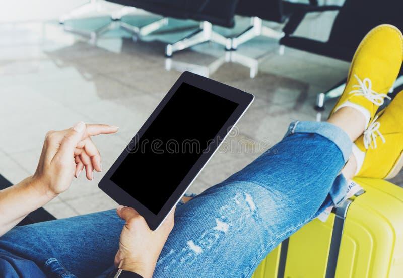 Menina nova do moderno que senta-se no aeroporto na bota amarela na mala de viagem que viaja em Europa, mãos fêmeas usando o app  foto de stock