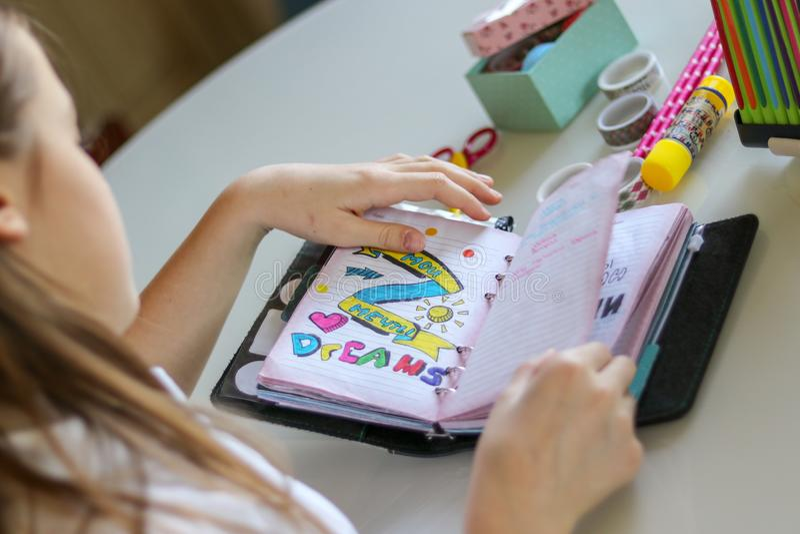 A menina nova do preteen que lança através de seu diário que escreve para baixo seus sonhos, assina meus sonhos no russo imagens de stock royalty free