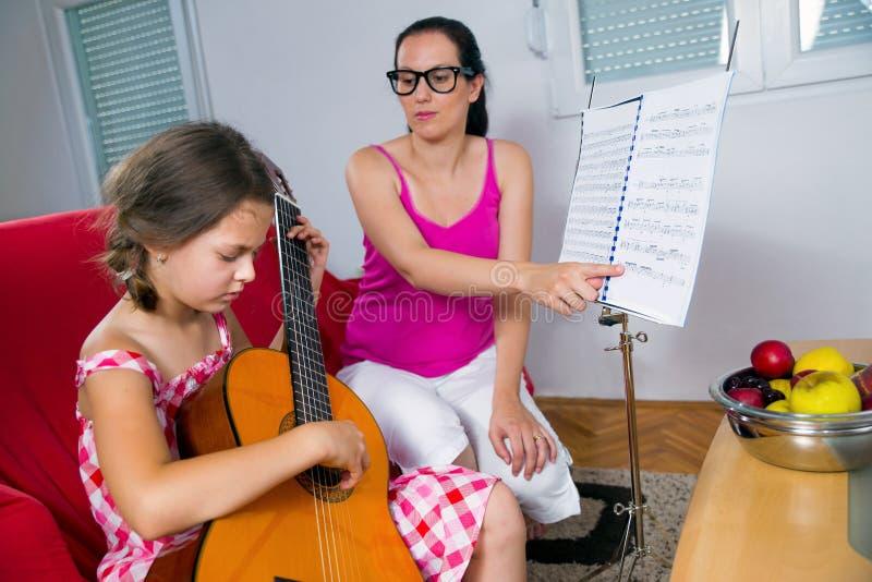 Menina nova do preteen que tem a lição da guitarra em casa fotografia de stock royalty free